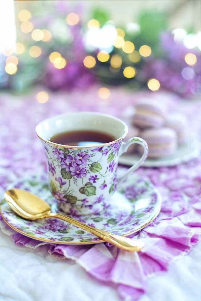 close up photo of a teacup with a purple floral pattern, matching saucer, gold spoon, and macrons out of focus in the background